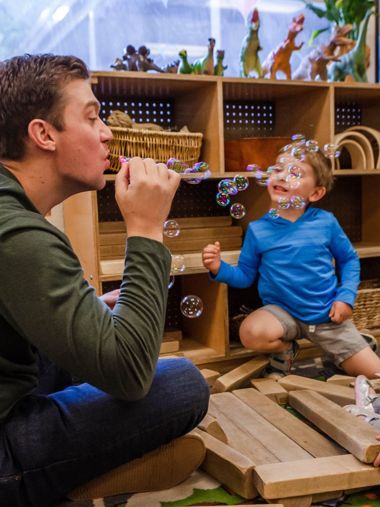 Man blowing bubbles with toddler